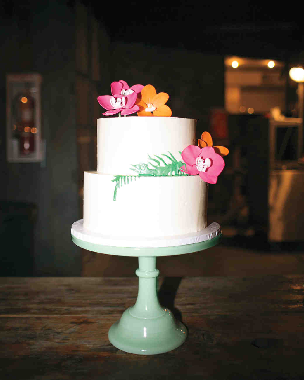 Two-Tiered White Wedding Cake with Bright Pink and Orange Flowers