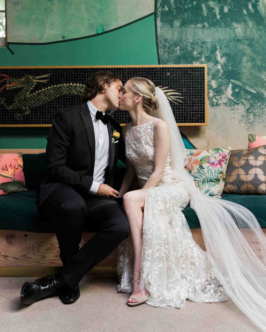 wedding couple kiss on couch with colored pillows