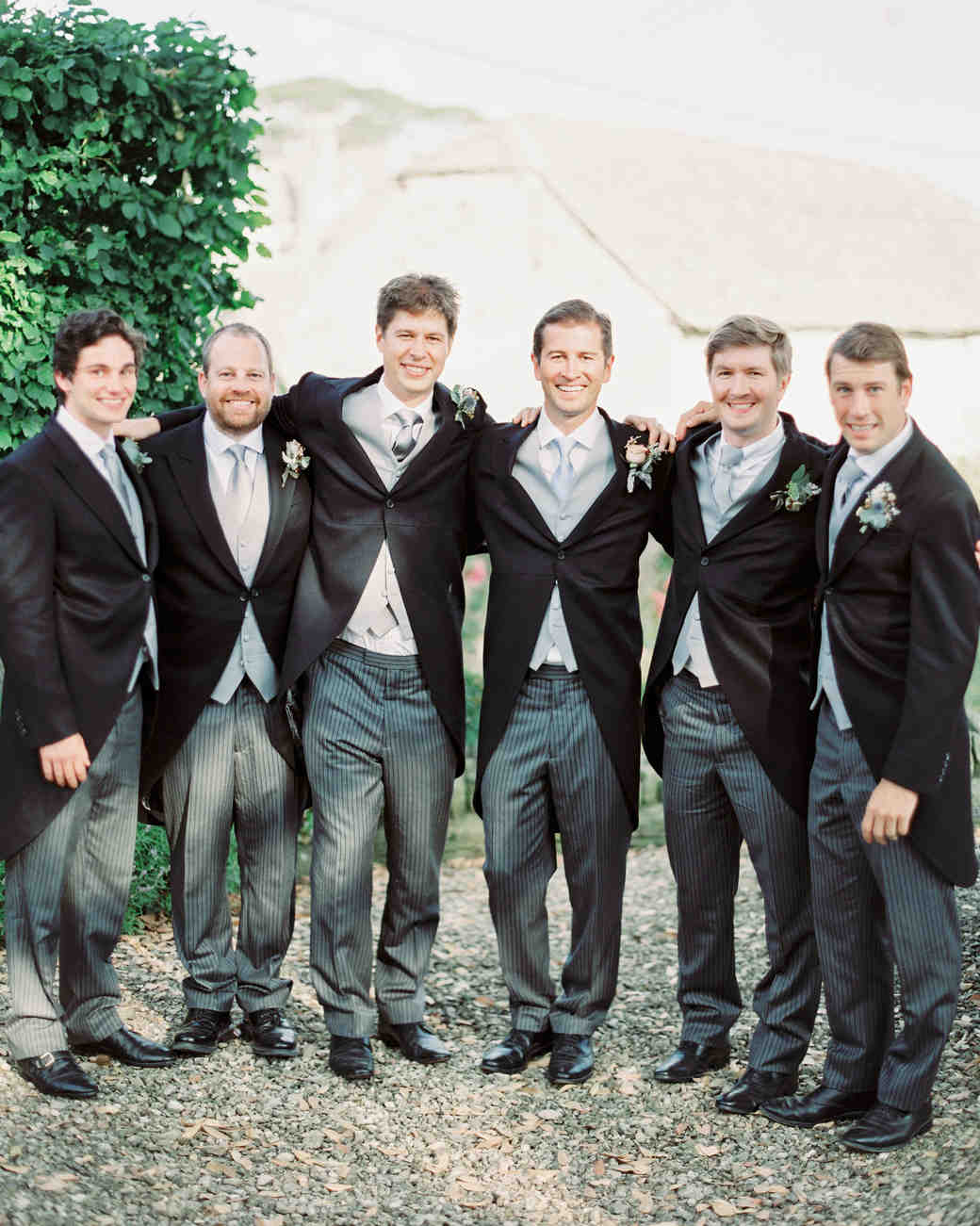 groomsmen wearing The Cotswold Tailor english coats and striped pants