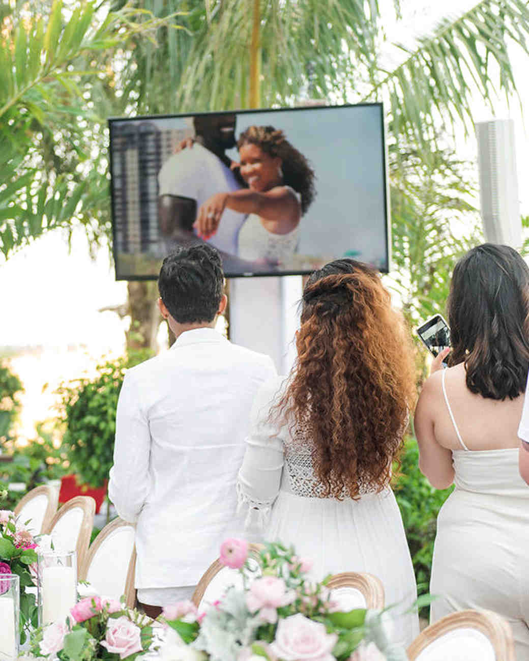 guests watching couple proposal video