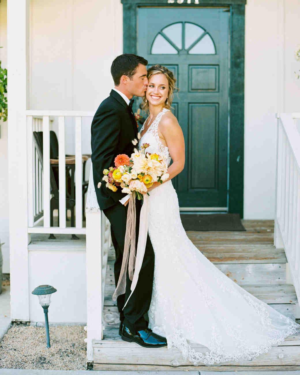 groom kisses bride on front porch steps