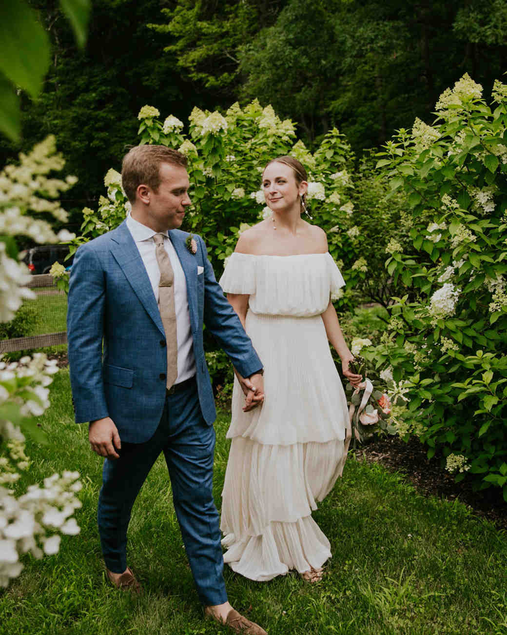 bride and groom walking through hydrangea bushes
