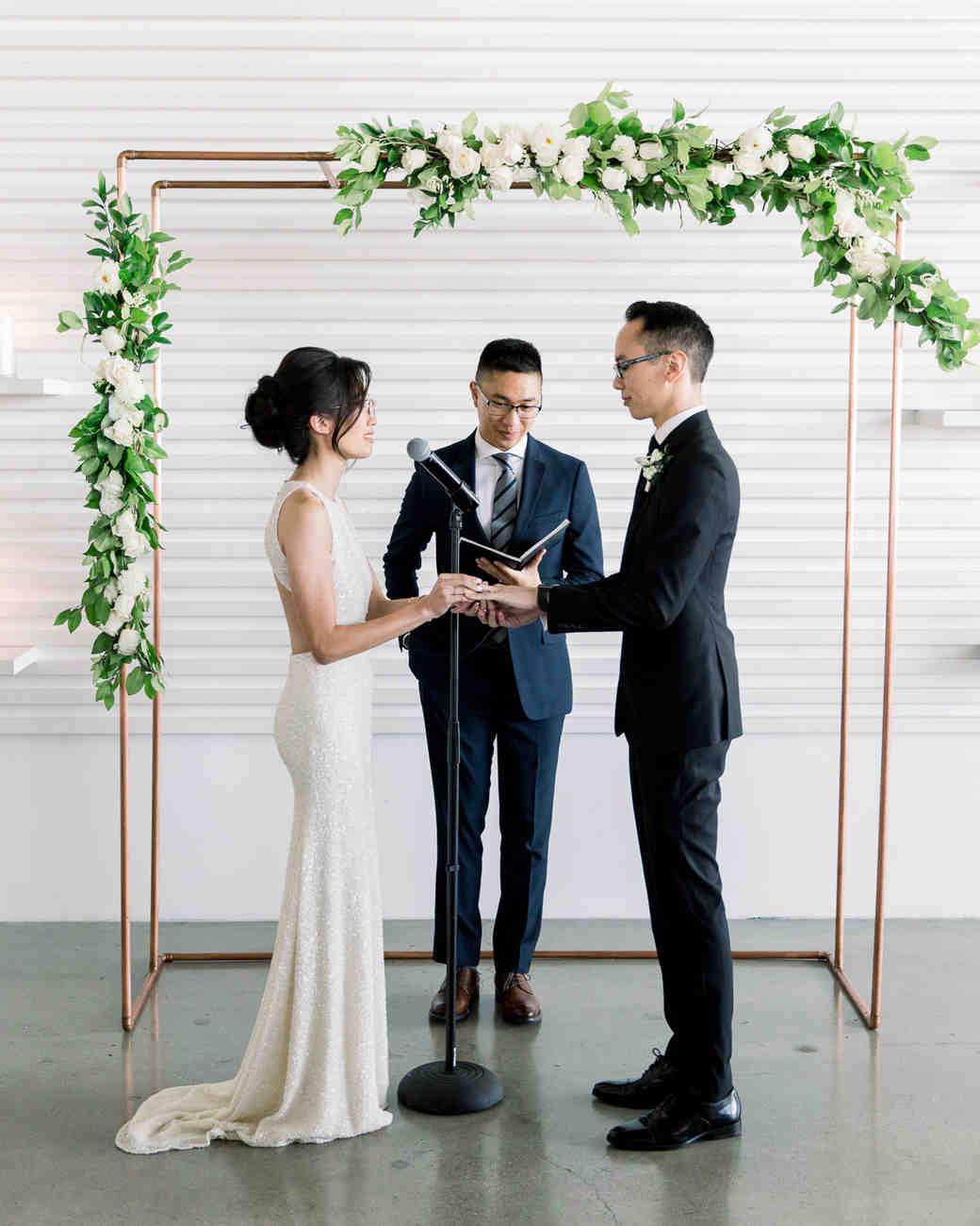 wedding ceremony bride and groom under white rose display