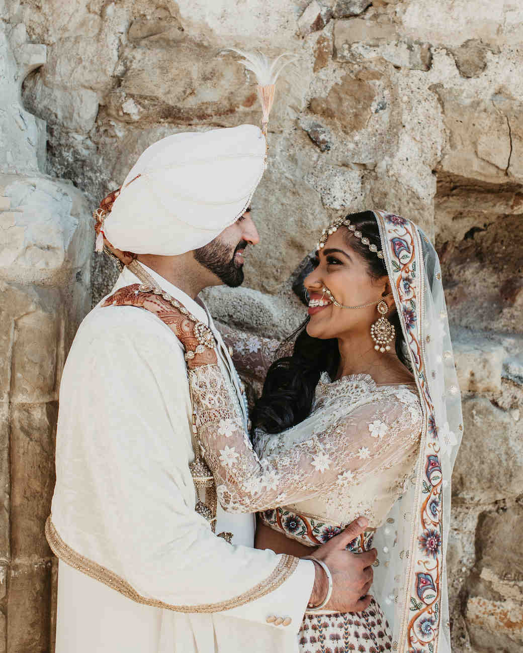 indian wedding bride and groom in front of rock wall