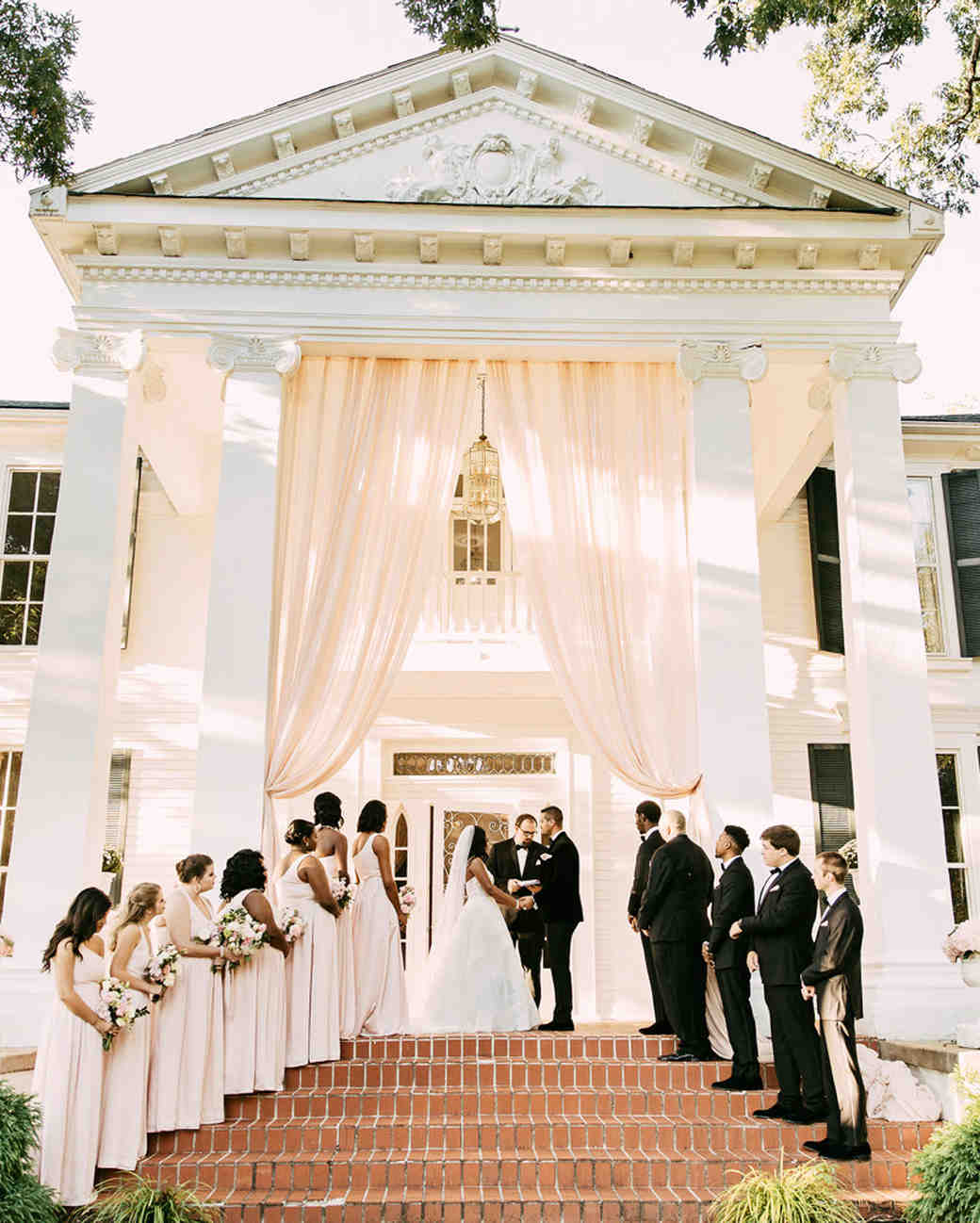 wedding ceremony on porch of mansion