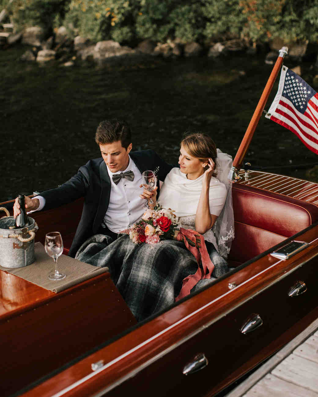 bride and groom sitting in vintage wooden Chris Craft boat