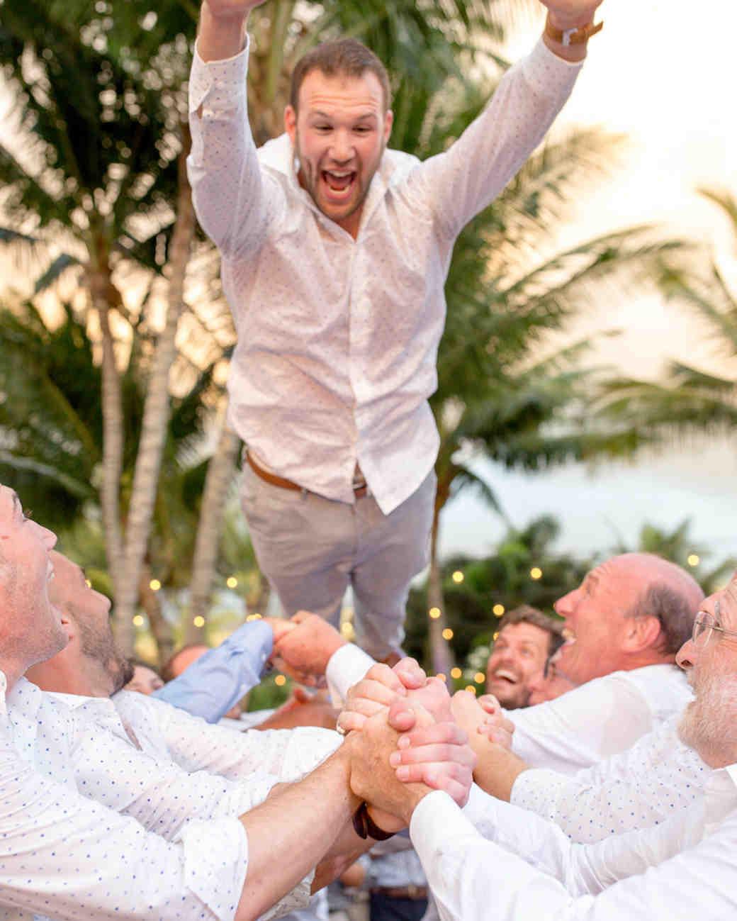 groom crowd surfs on groomsmen during reception