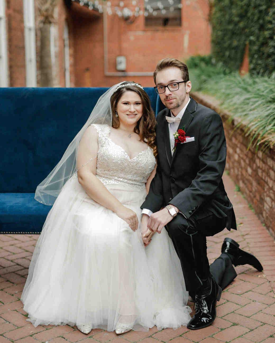 elizabeth seth wedding groom kneeling by bride sitting on blue couch