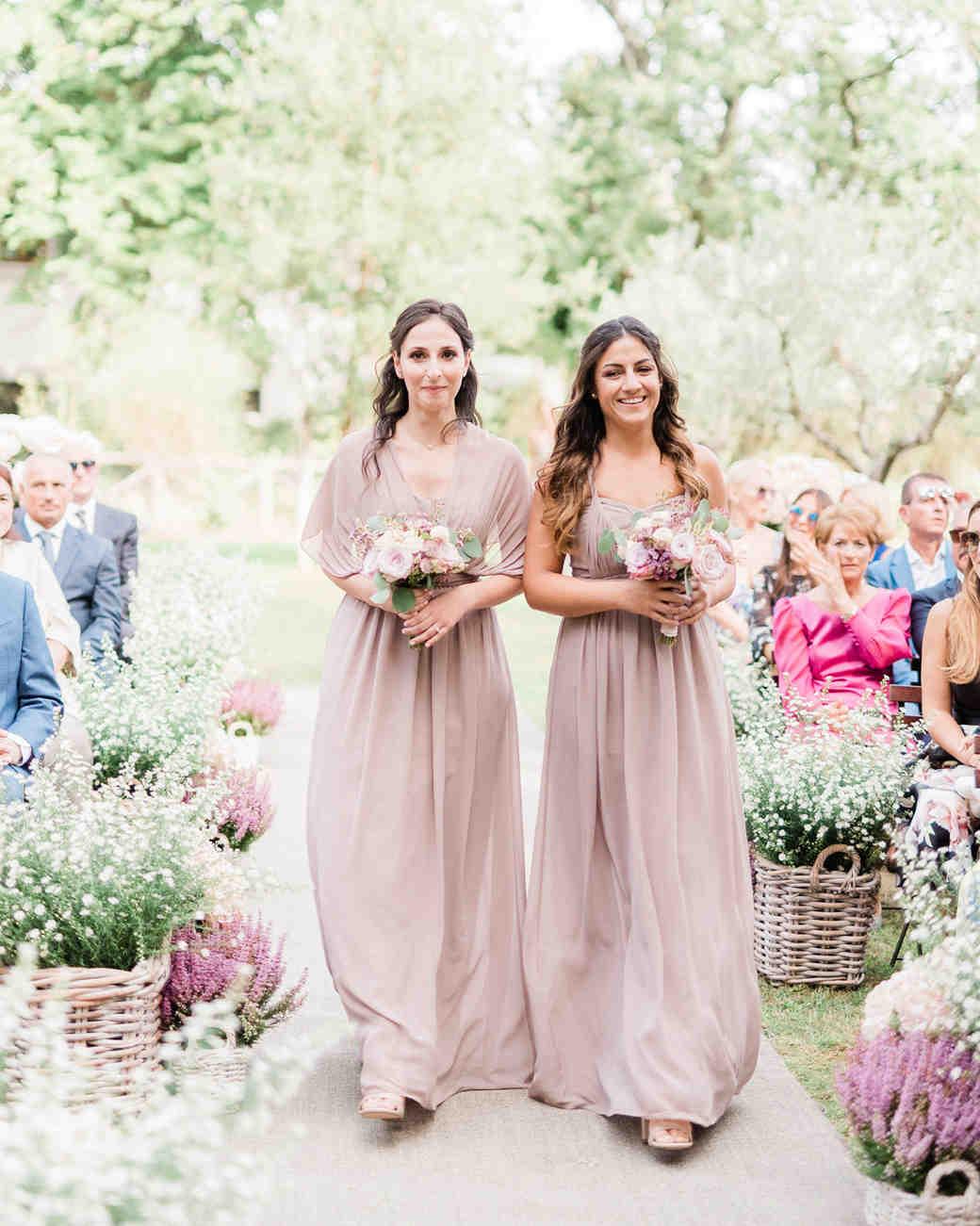 two bridesmaids walking down wedding aisle wearing mauve dresses
