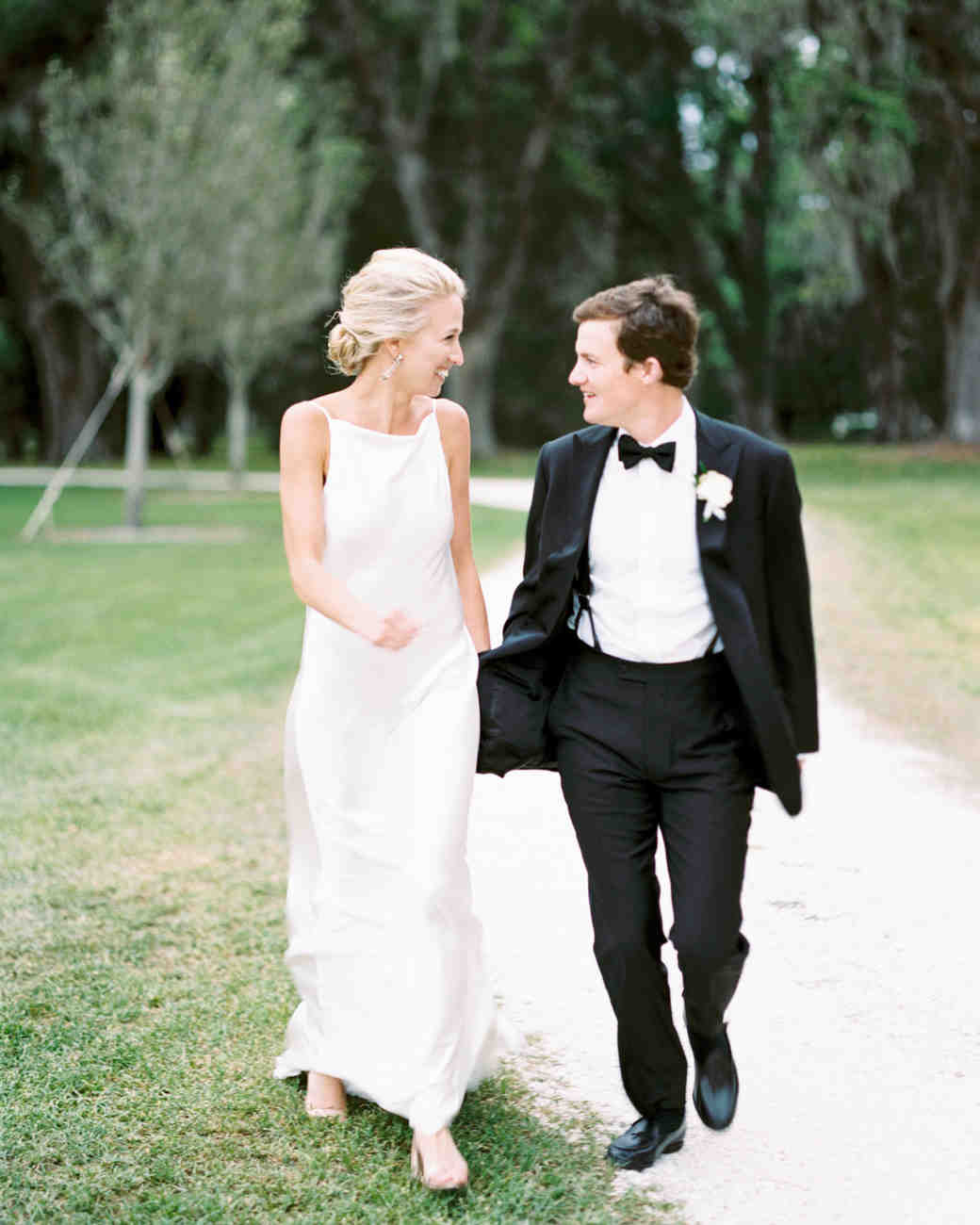 bride and groom smile at each other outside on pathway
