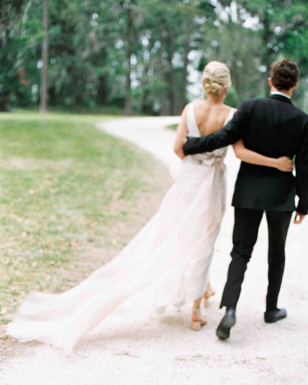 bride and groom walk away with arms behind each others back