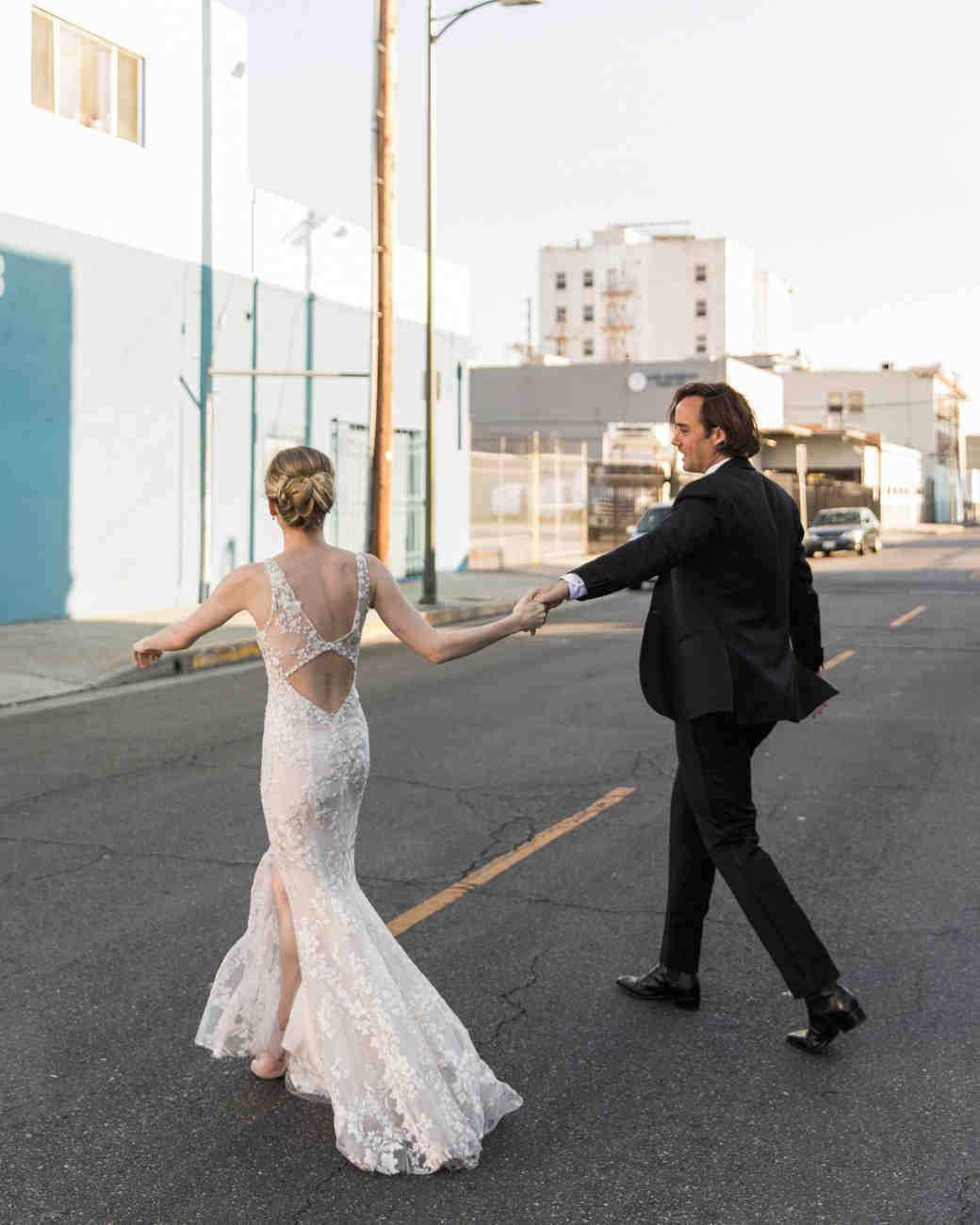 wedding couple hold hands walking across street in wedding clothes