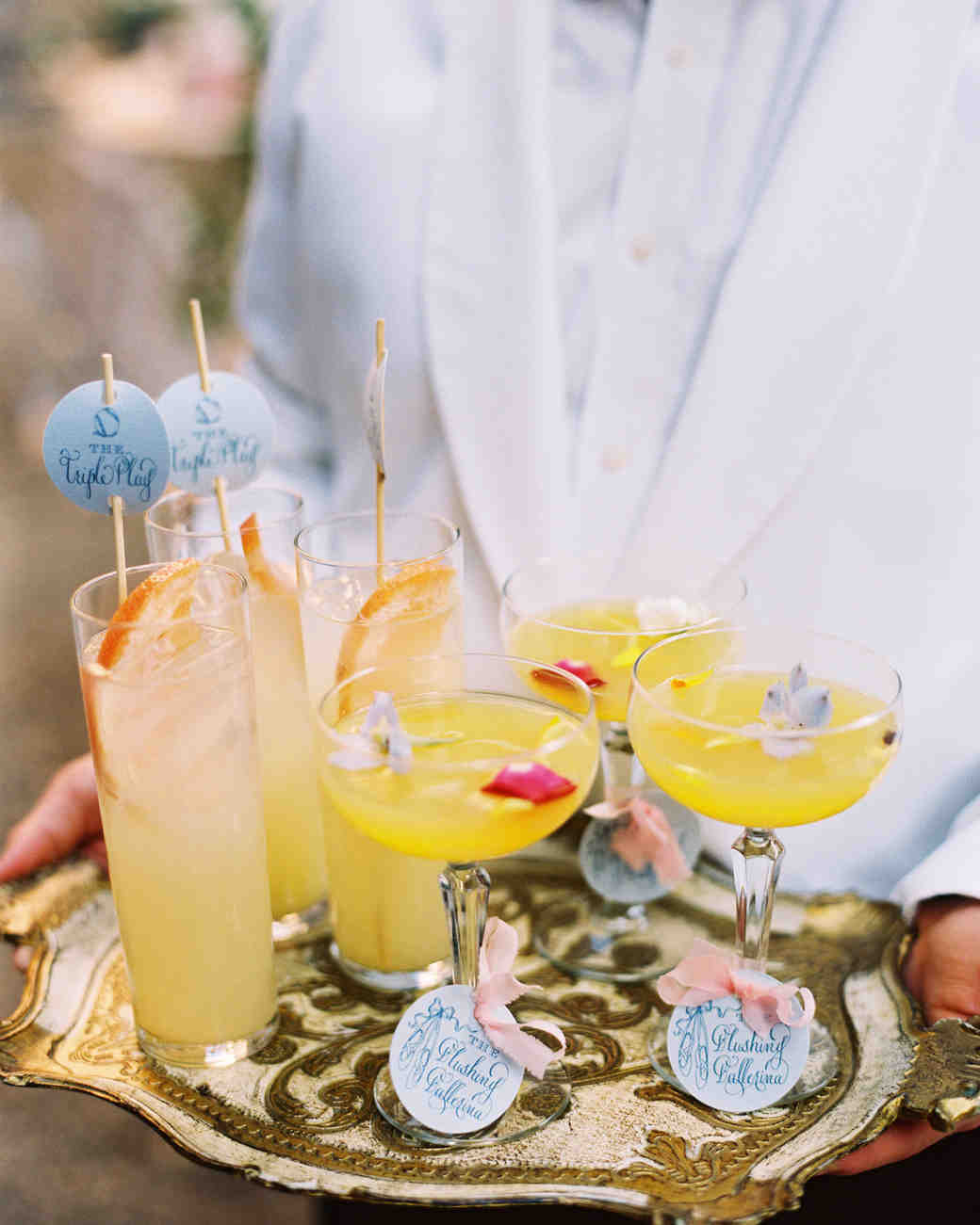 server holding cocktail hour tray with drinks