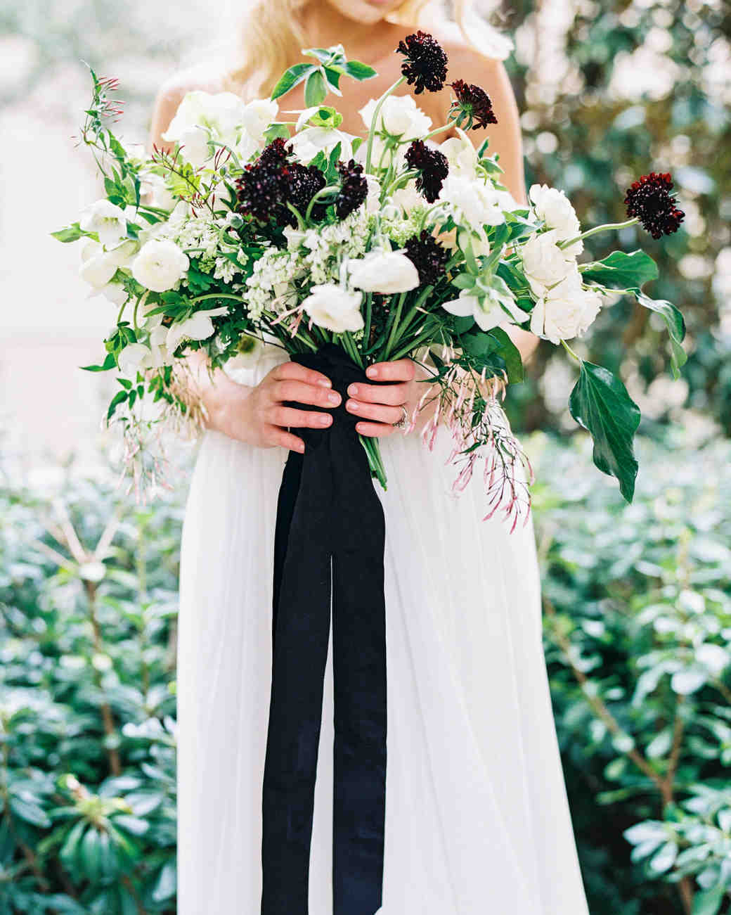 bride holding a black and white bouquet with ribbon