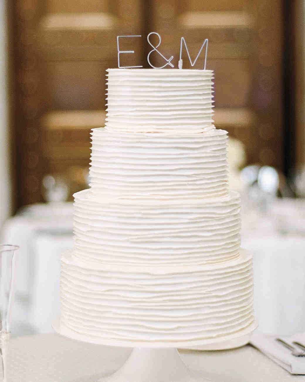 Four-Tiered White Wedding Cake with Layered Icing and Aluminum Initials Topper