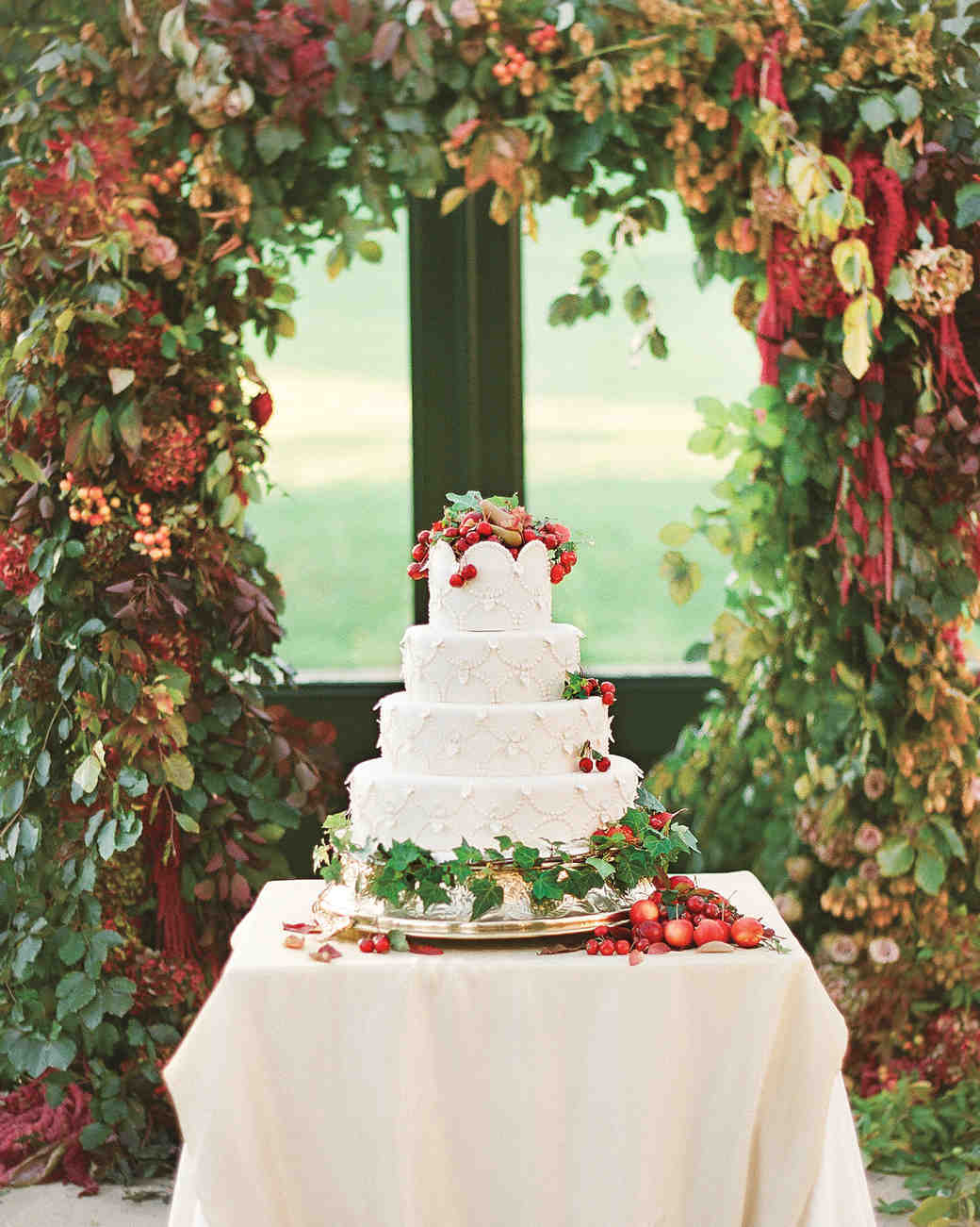 Four-Tiered White Wedding Cake with Piping and Ivy, Crabapples, and Mini Pears
