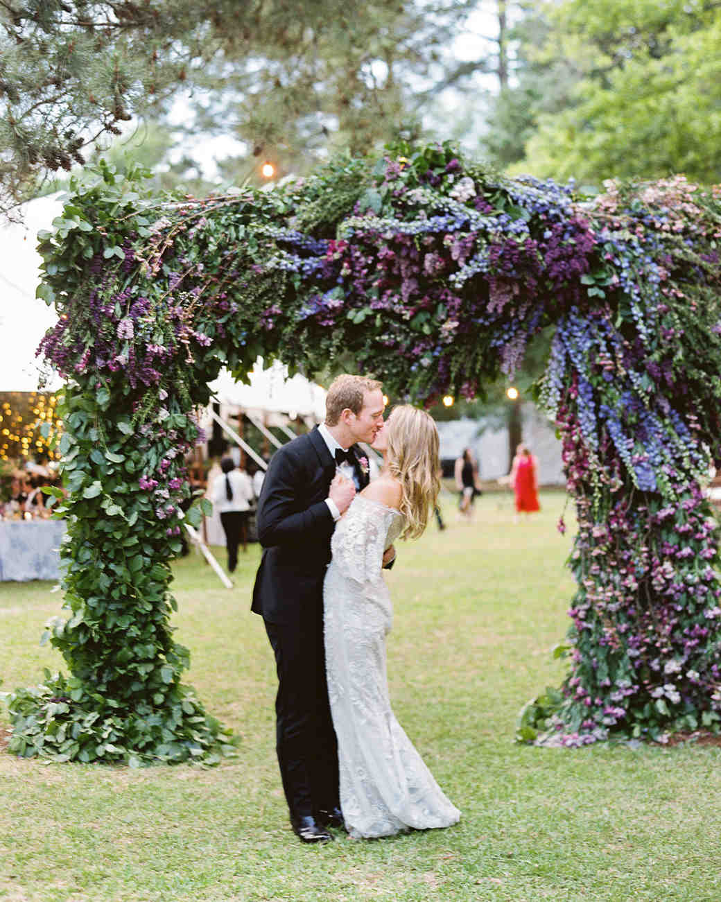 julia mitchell wedding couple kissing beneath arch