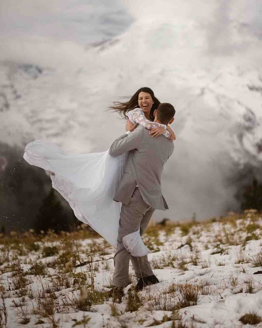 groom carrying bride in snow