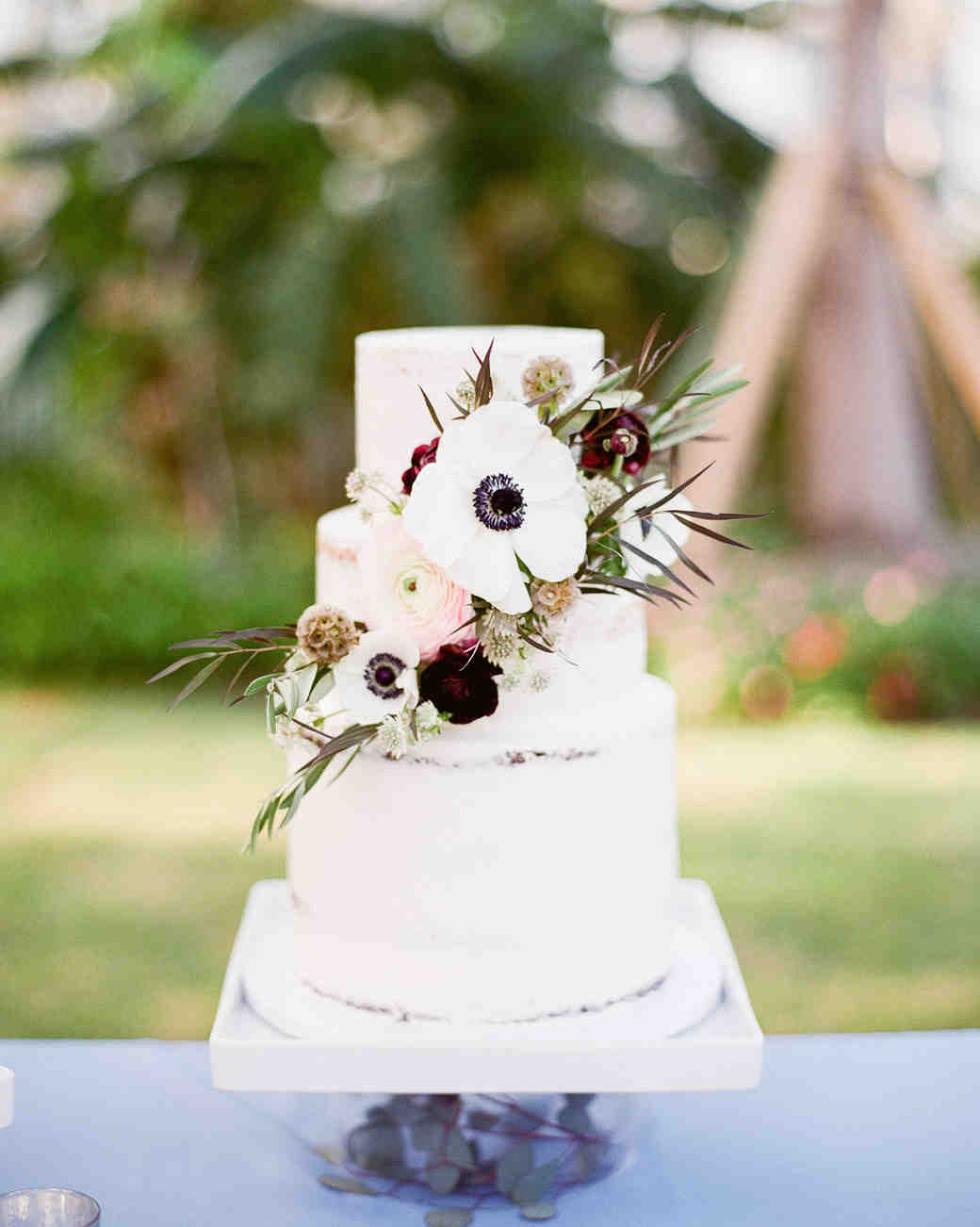 white frosted wedding cake topped with floral arrangement
