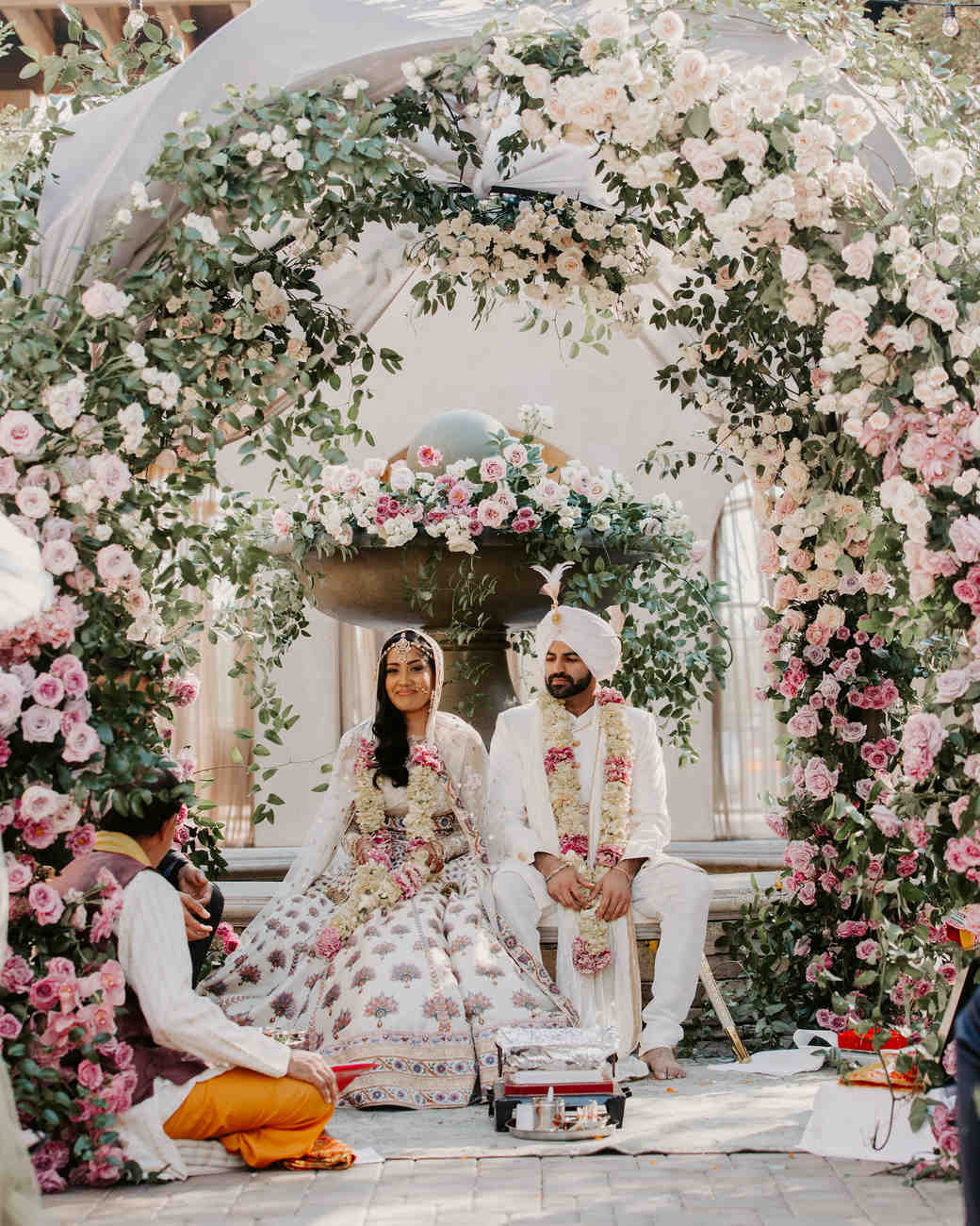 indian wedding bride groom sitting below floral arch