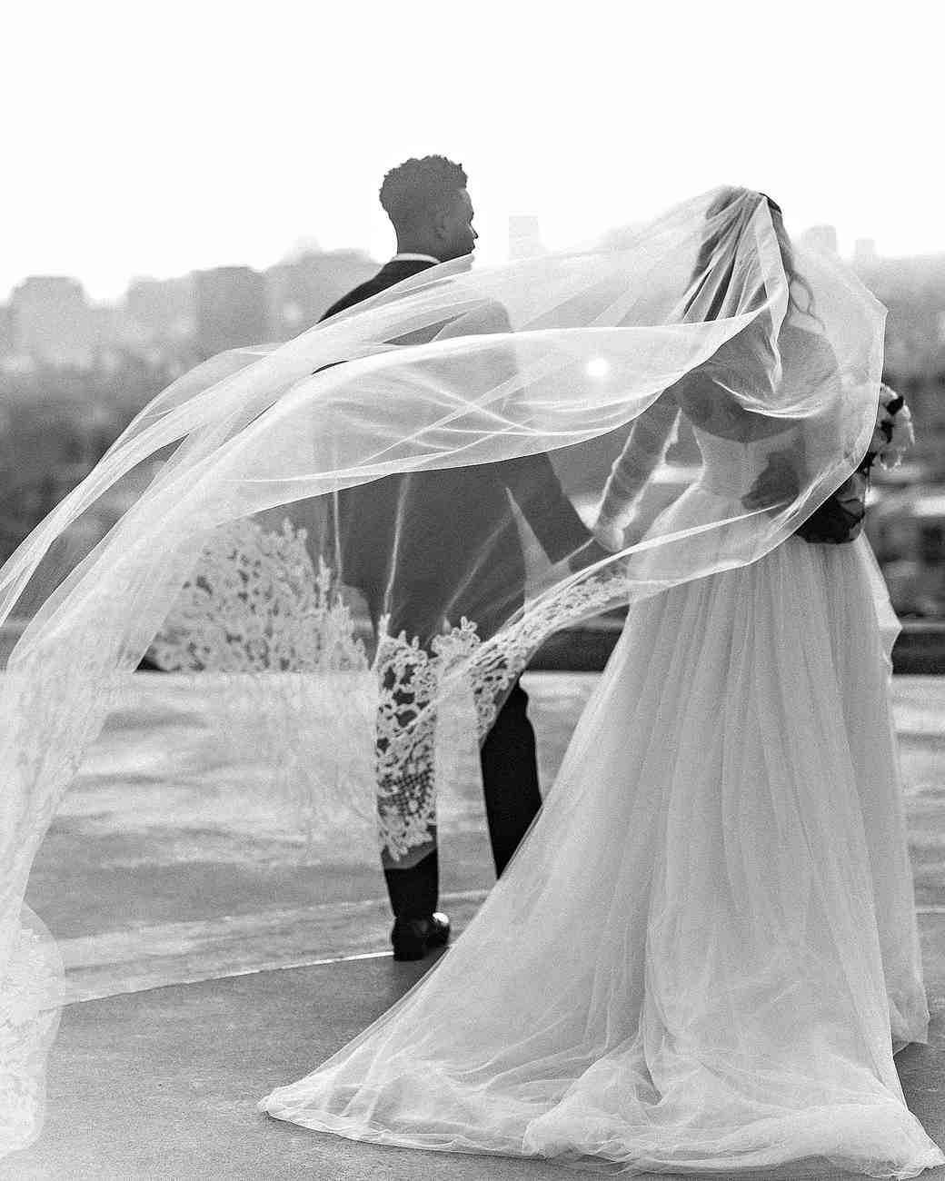danielle kevin wedding couple holding hands veil in the wind