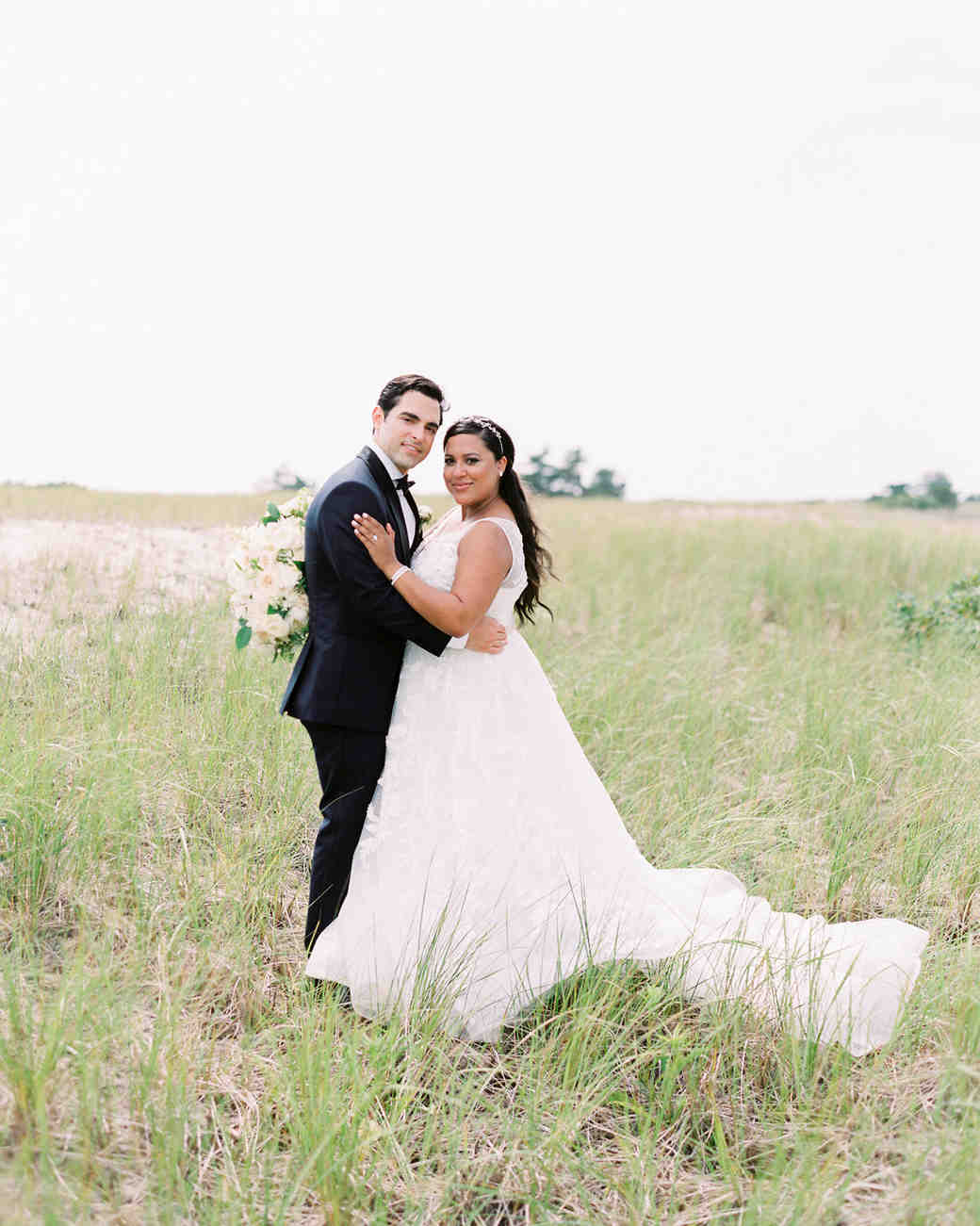 bride and groom posing in field of tall grass