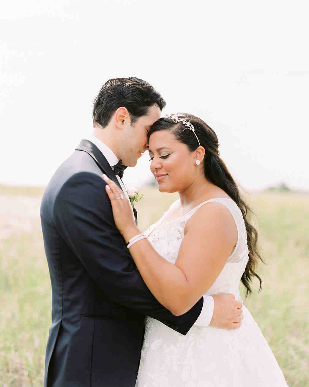 bride and groom embracing in field of tall grass