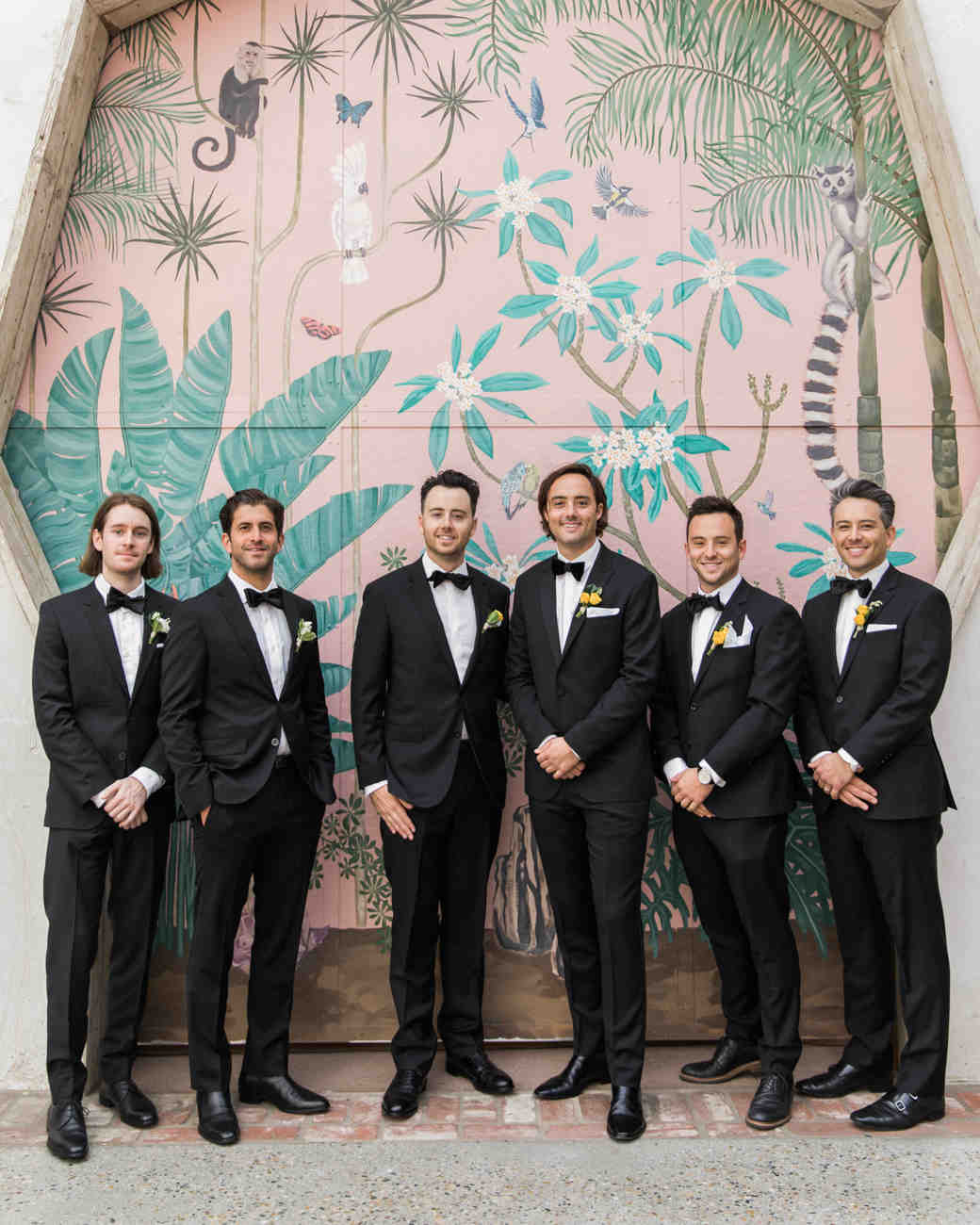 groom and groomsman posting in front of painted wall