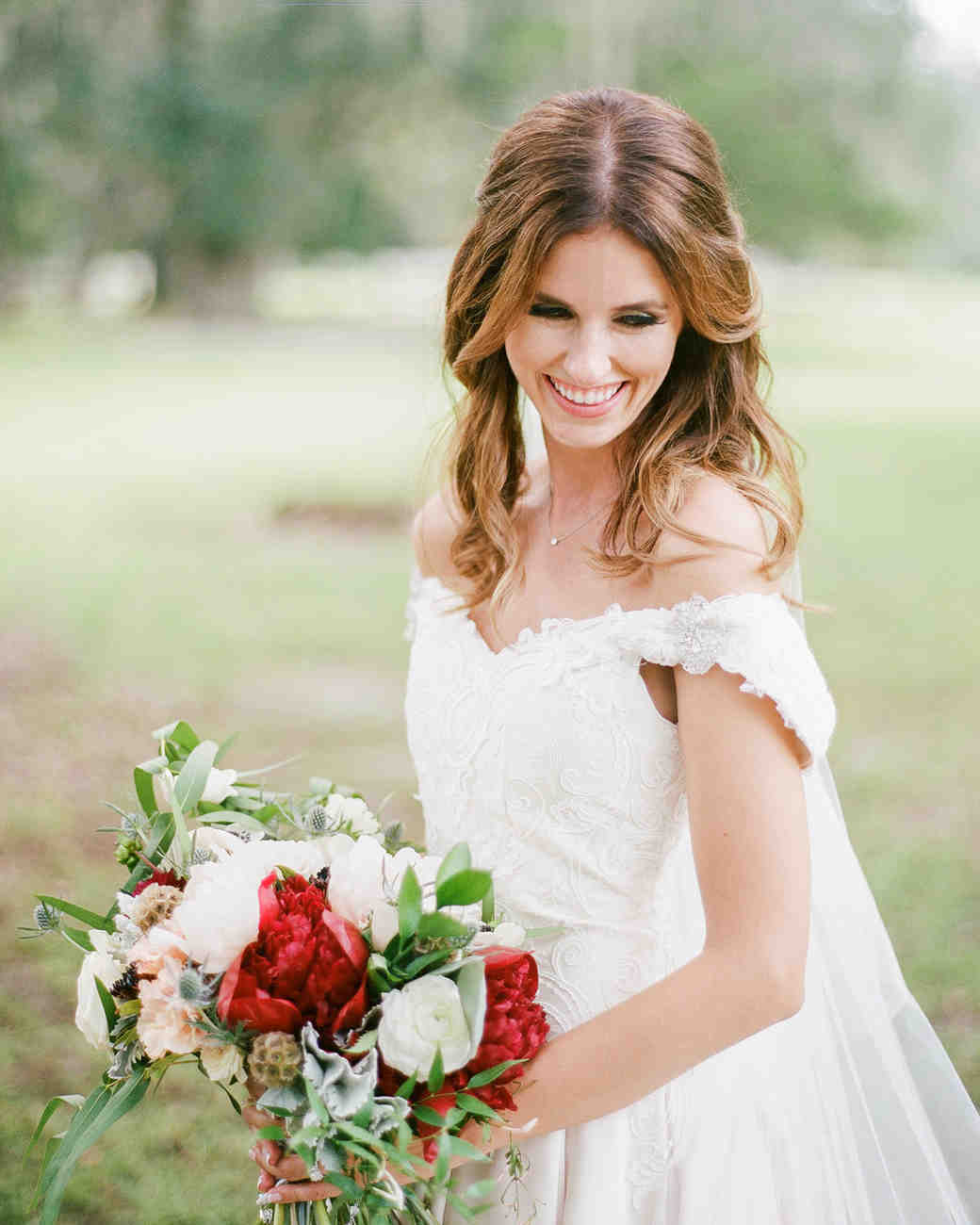middle part hairstyles bride smiling holding red and white bouquet