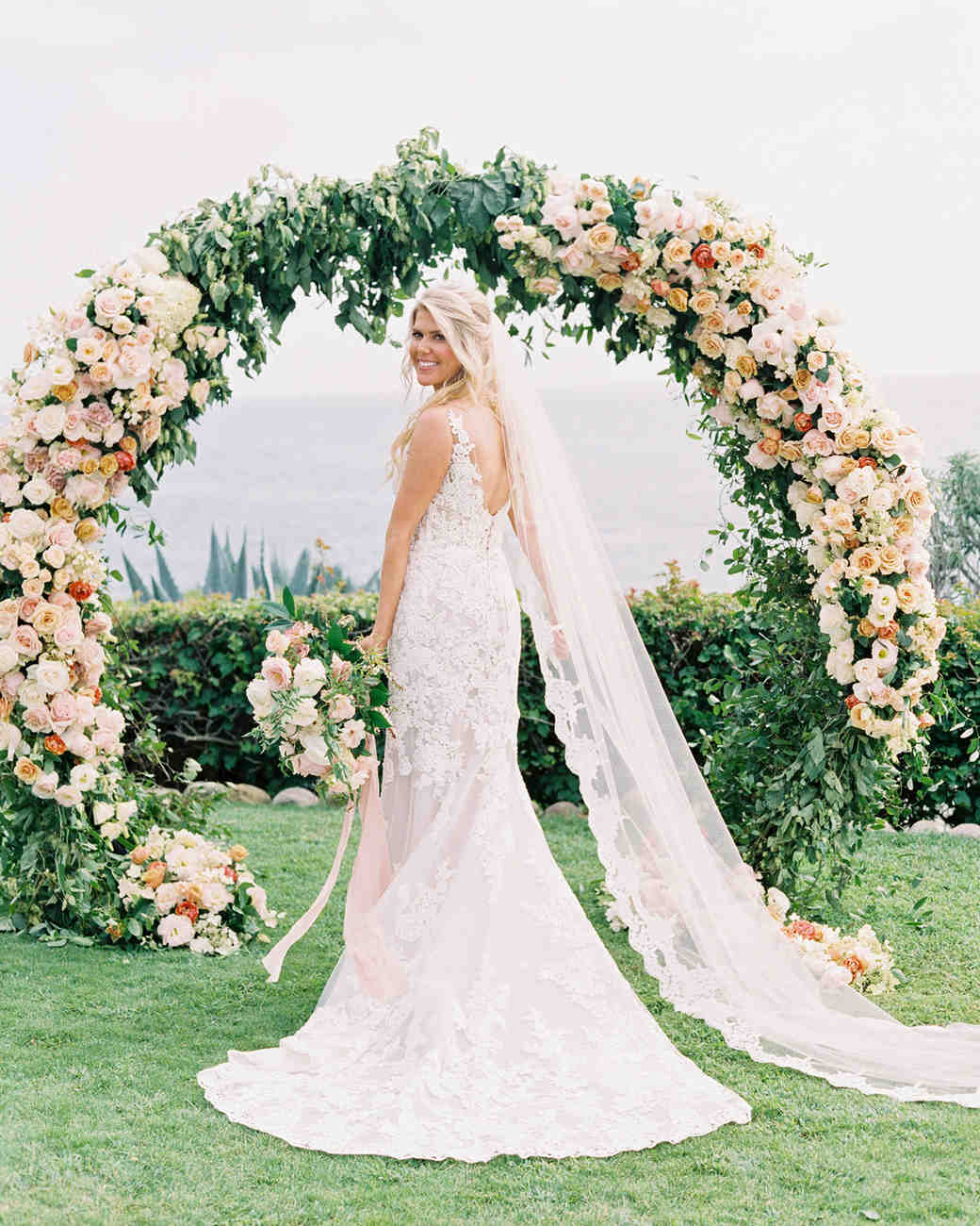 mykaela and brendon wedding bride standing beneath ceremony arch of roses