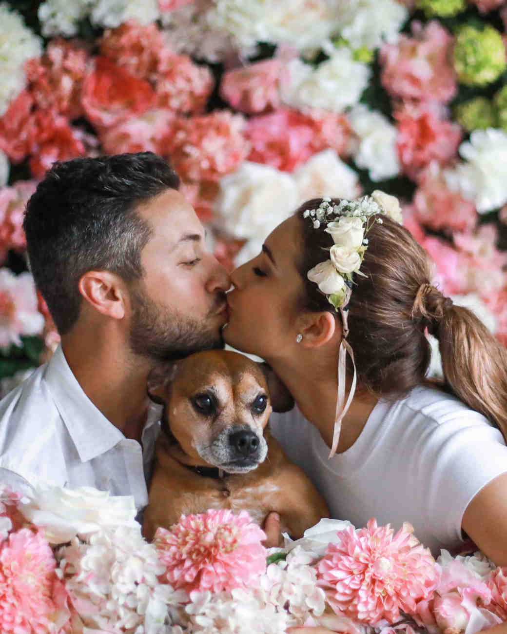 couple kiss with puppy pink and white flowers