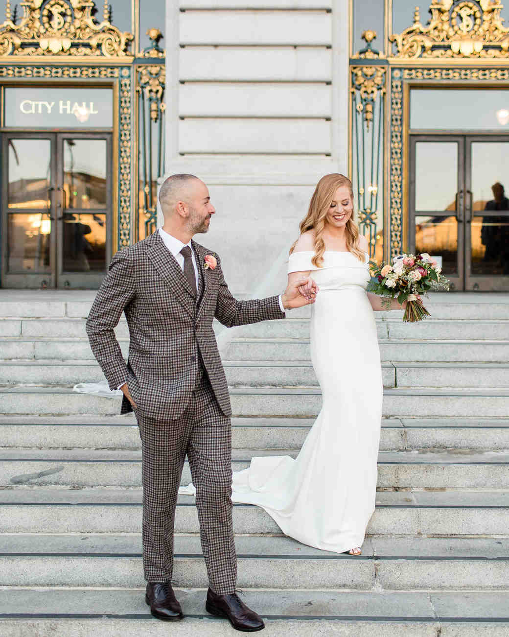 groom wearing plaid brown suit holding bride's hand on city hall steps
