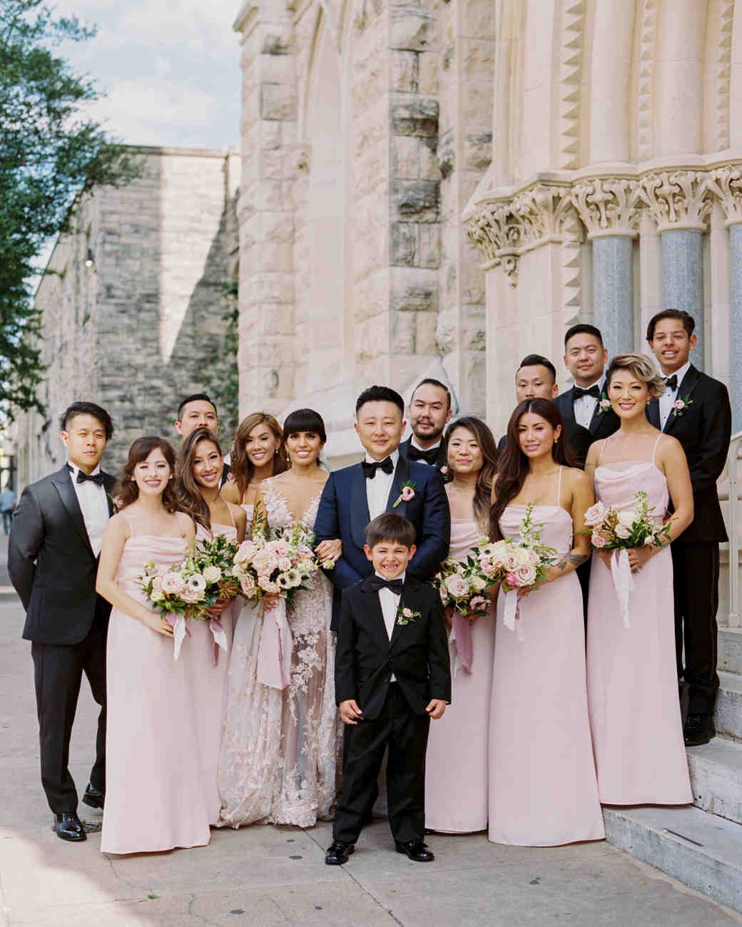 wedding party pose together outside in front of cathedral