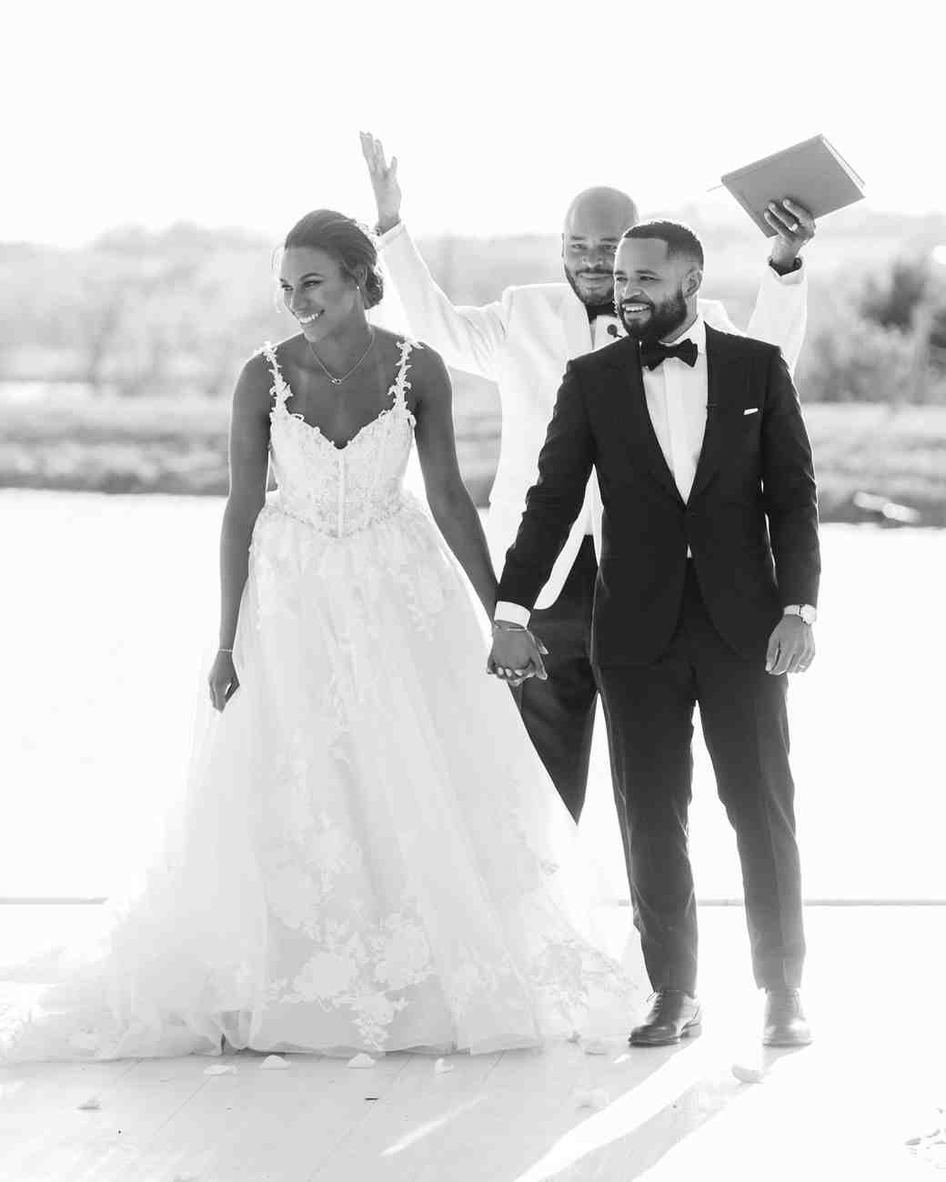 black and white bride and groom smiling at guests