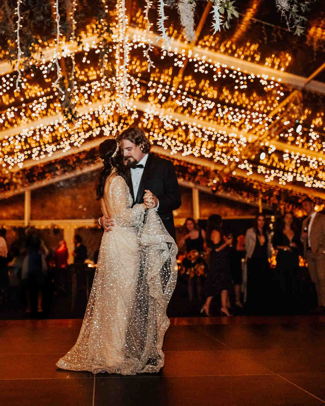 bride and groom share first dance under a ceiling of string lights