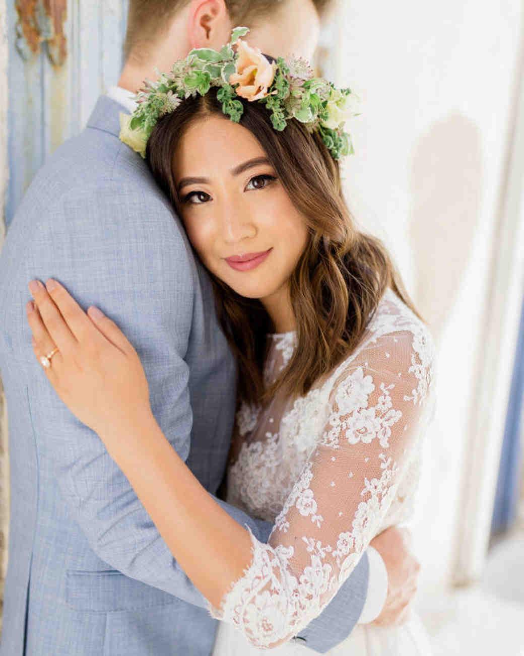 middle part hairstyles bride wearing flower crown hugging groom