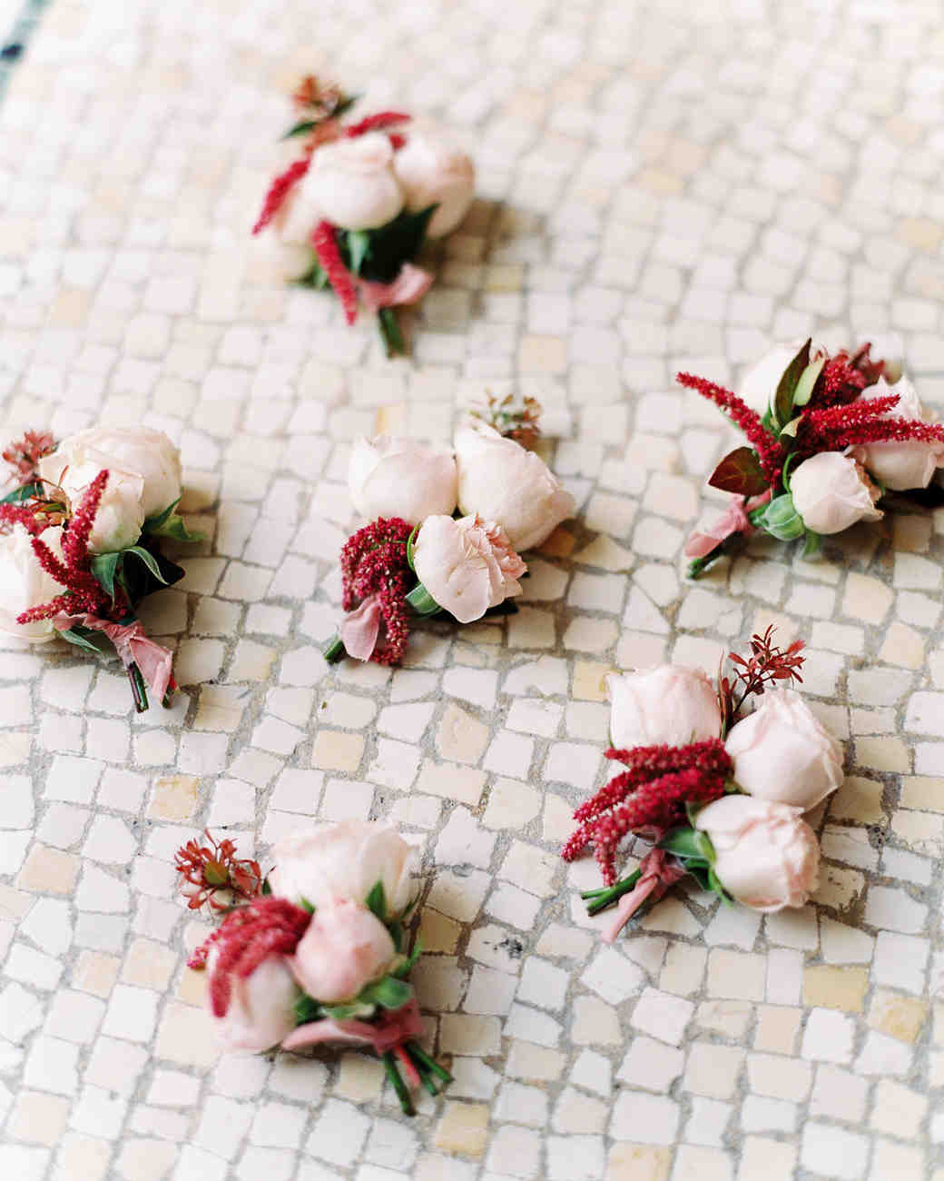 red and white floral boutonnieres with greenery accents