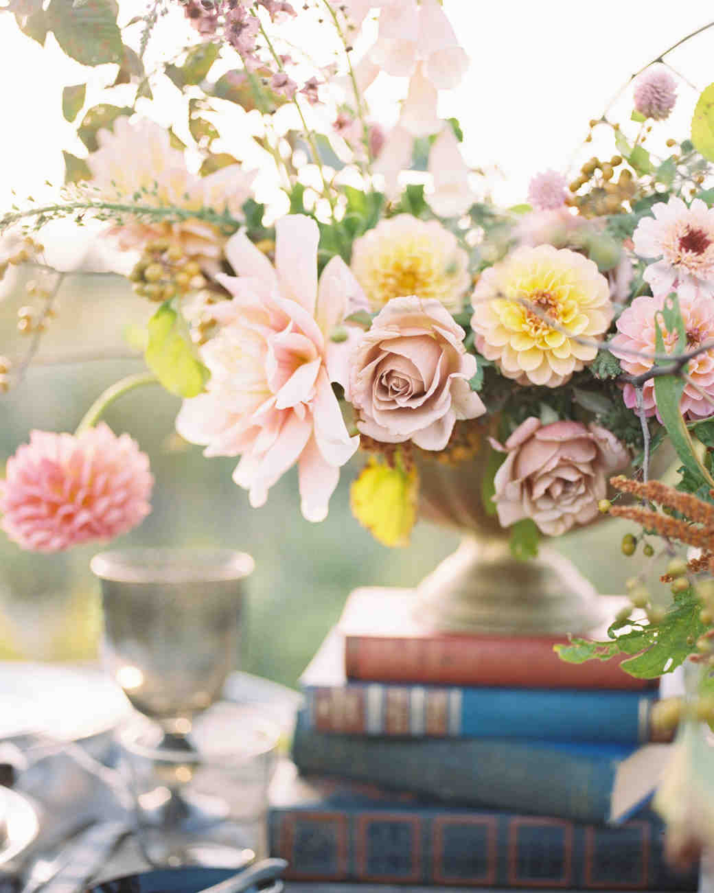 dusty pink garden rose centerpiece on top of vintage books