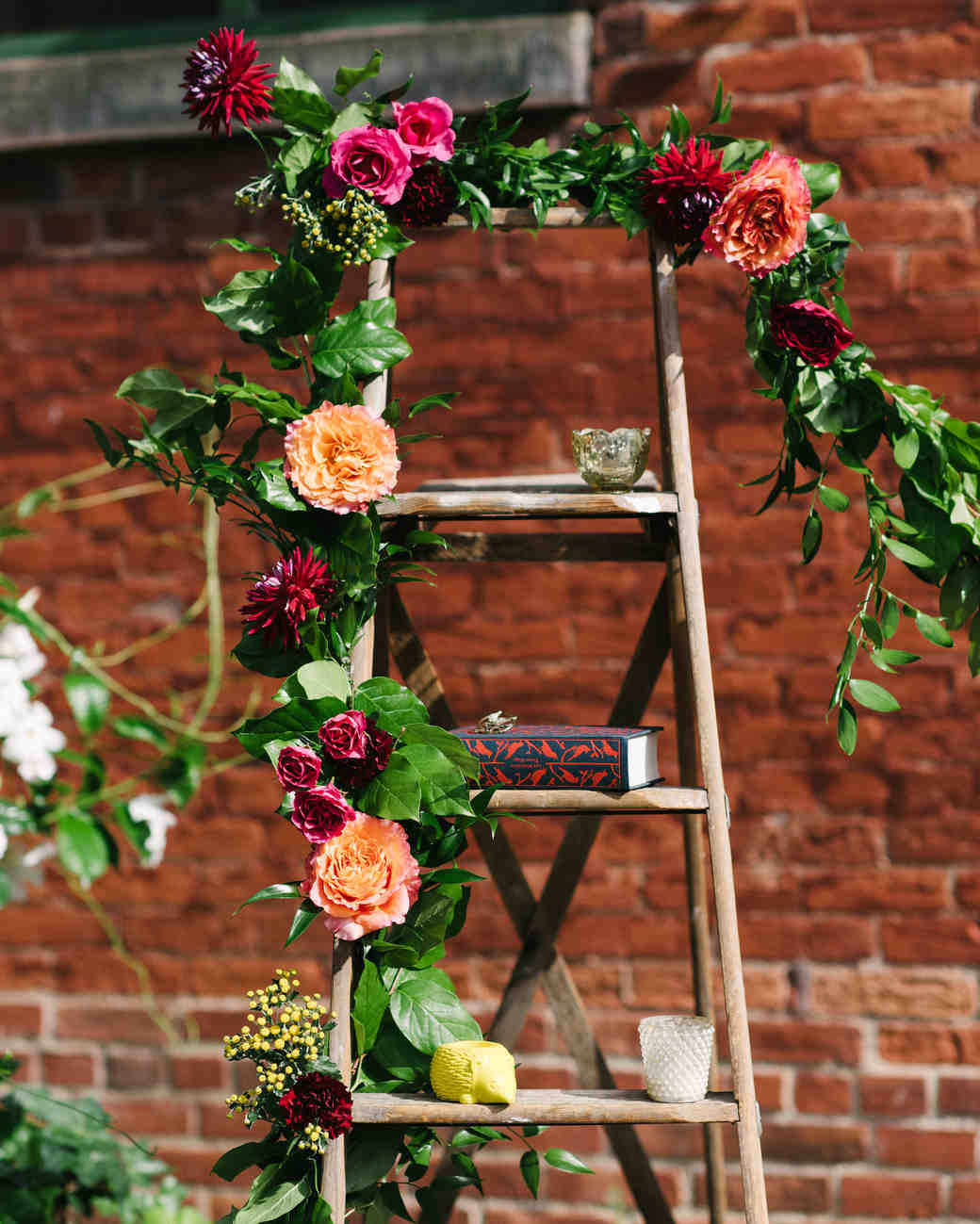 steph tim wedding ceremony ladder brick and flowers backdrop