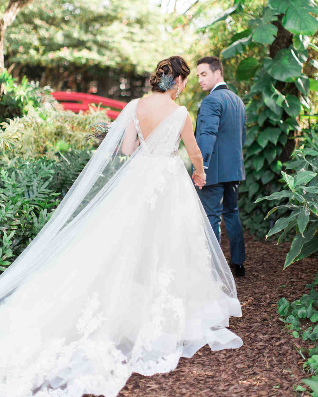 bride and groom walking away surrounded by greenery