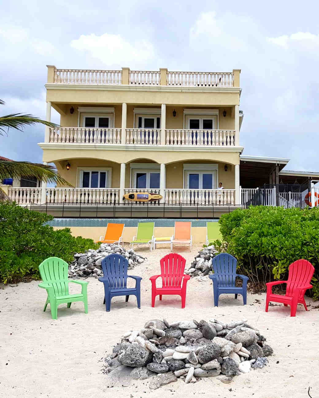 air bnb wedding venue beach with multi-colored chairs and stone fire pit