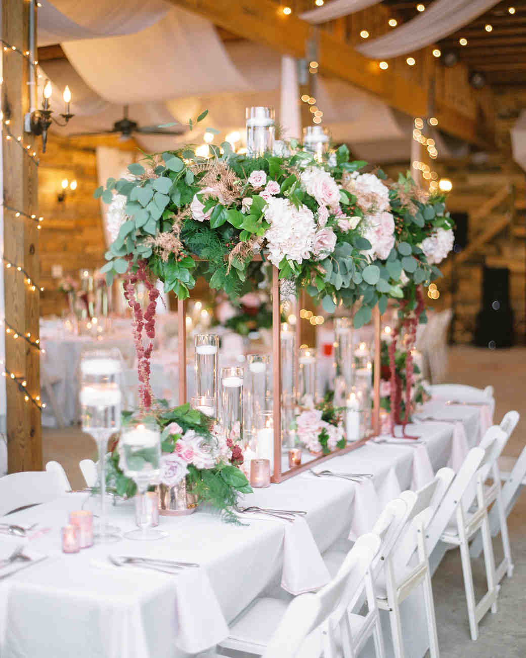 white linen tables decorated with floating candles and pink and red florals