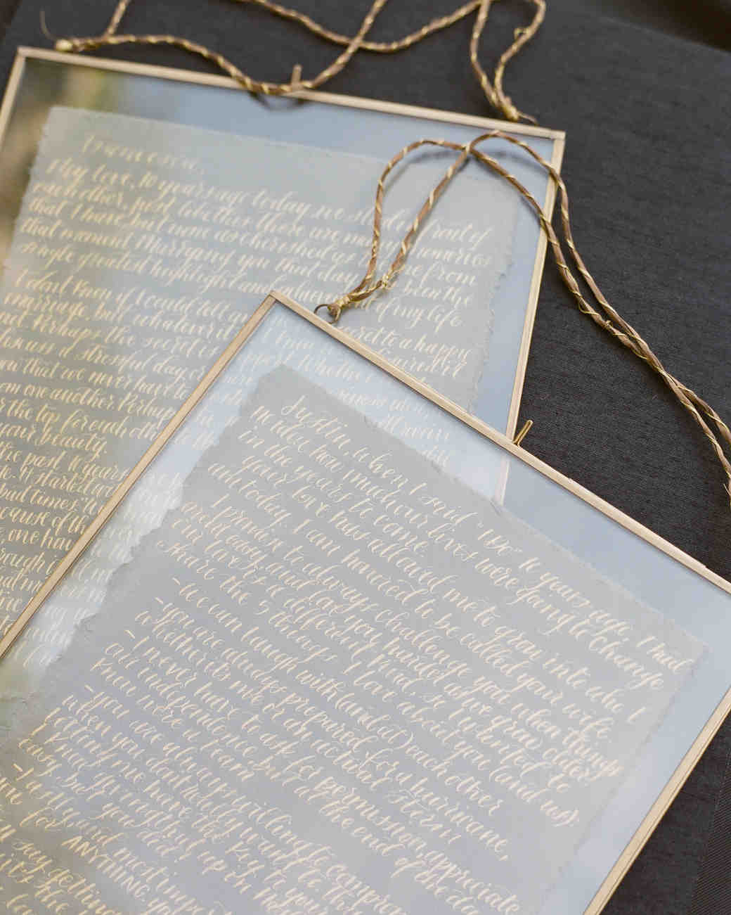handwritten vow renewals displayed in glass frame with gold trim