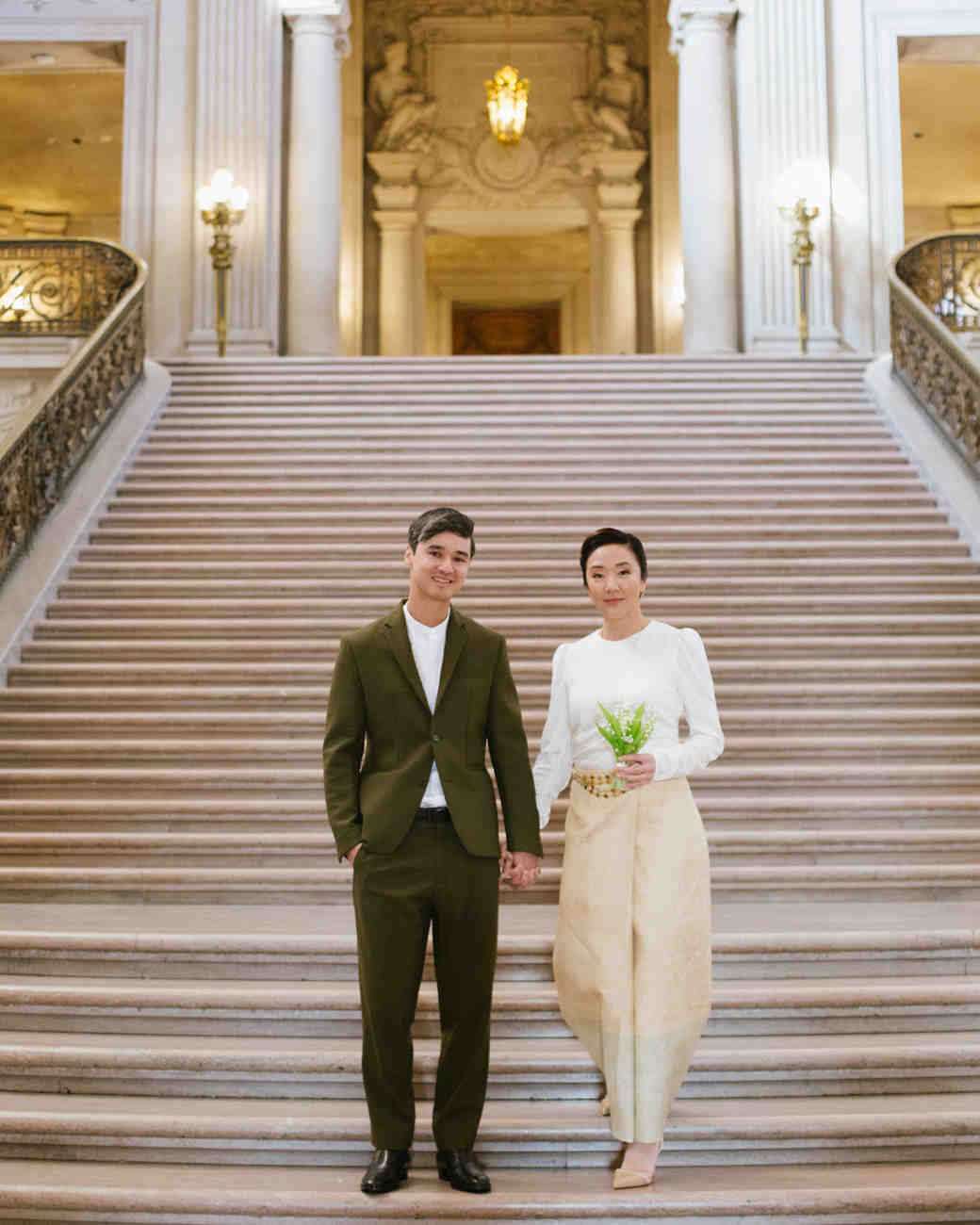 bride and groom standing on San Francisco City Hall steps