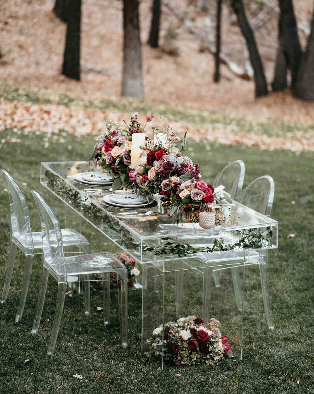 lucite table and chairs with rose floral arrangement set up on a lawn