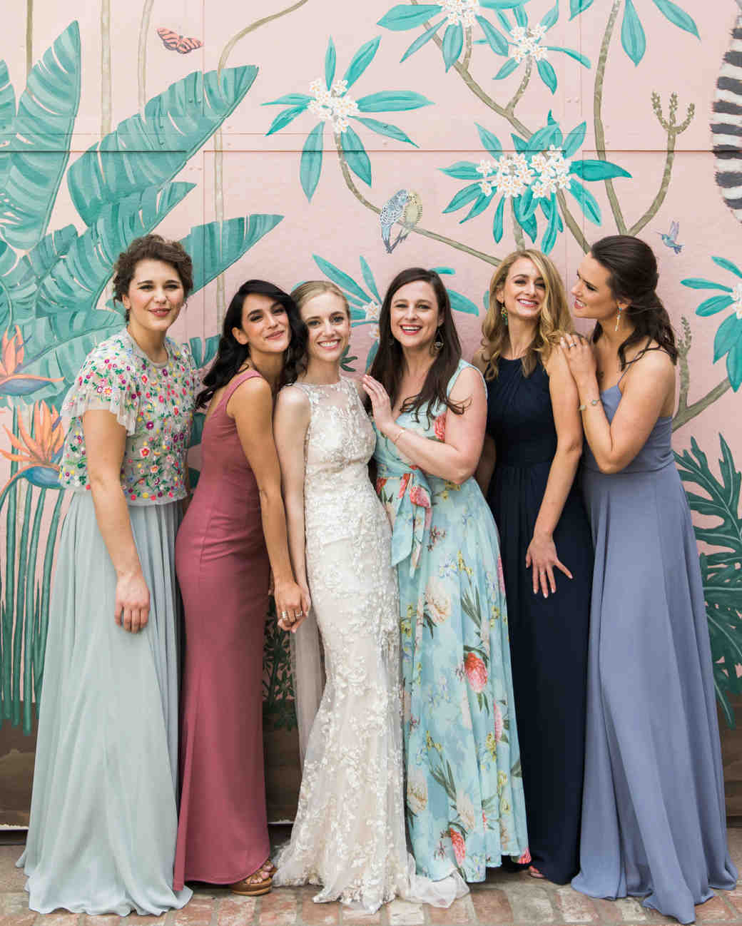 bride with bridesmaids in different dresses in front of painted wall
