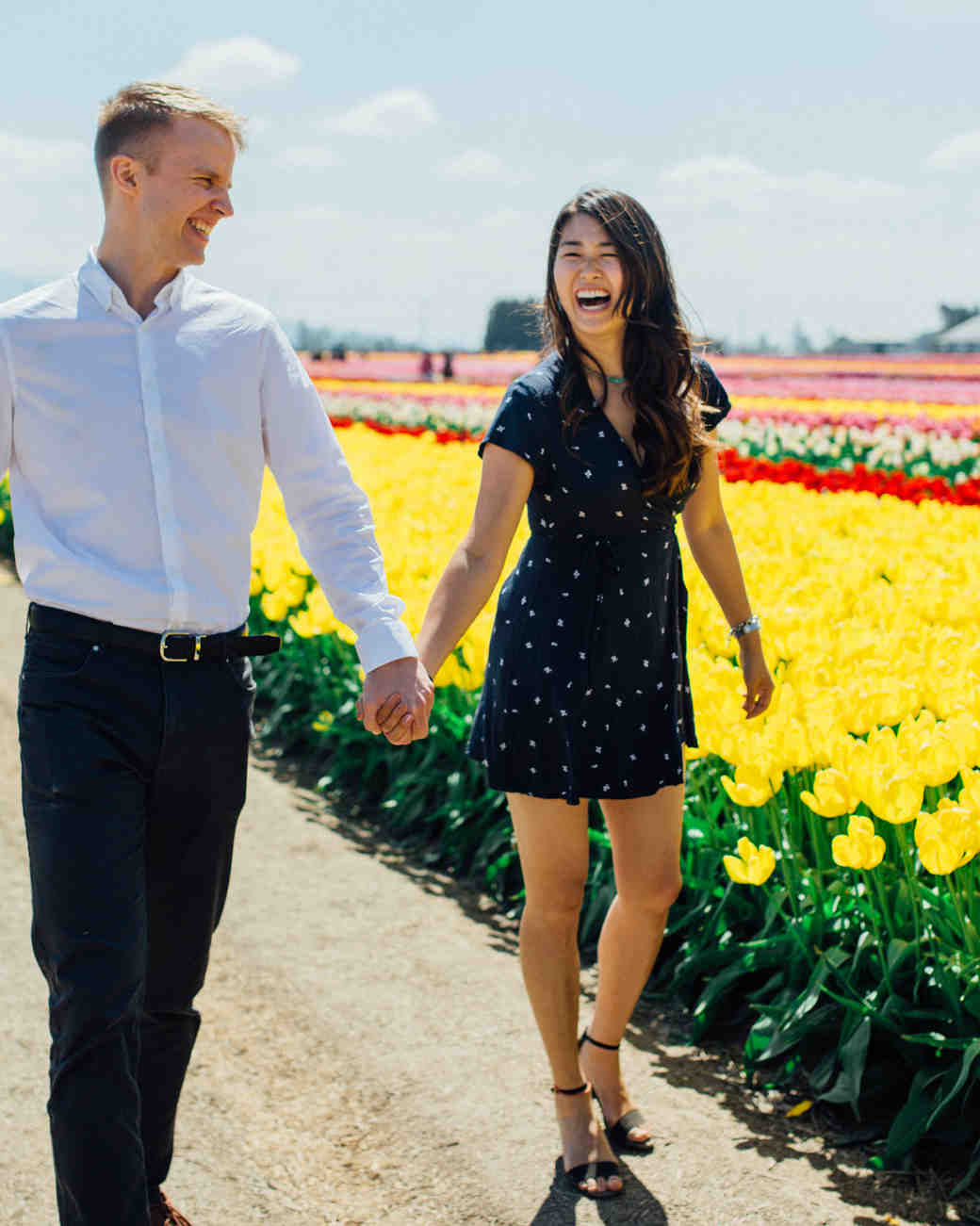 couple walking in flower field summer engagement photos