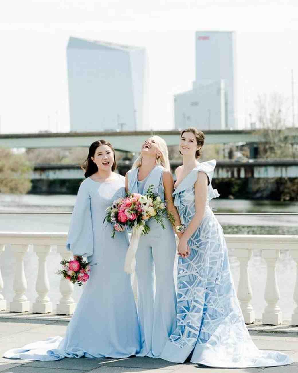 women standing on bridge wearing pale blue bridesmaid dresses and jumpsuit