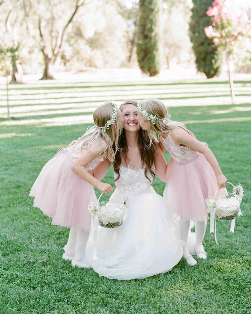 two flower girls holding white wire baskets