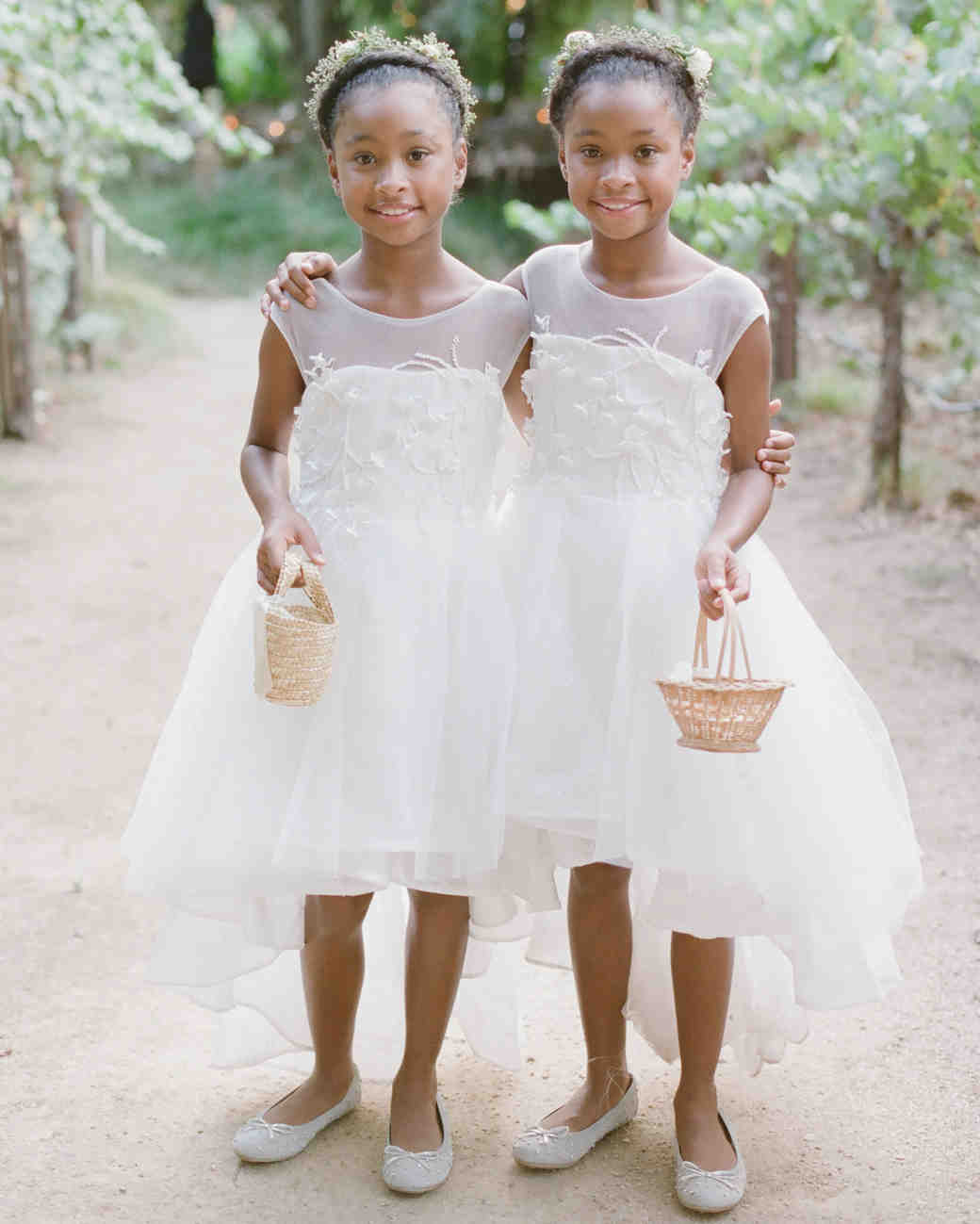 two flower girls holding small wicker baskets